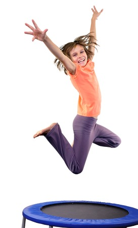 Portrait of a cute elementary girl jumping and dancing.  Isolated over white background