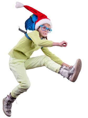 hurrying: Christmas girl with Santa red hat with a backpack hurrying up, running and jumping. Isolated over white background. Education childhood concept Stock Photo