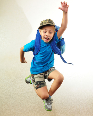 Portrait of a schoolchild with backpack leaping . Childhood, education, learning concept Stock Photo