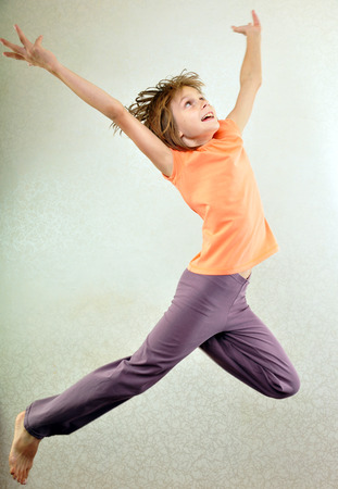 Portrait of a cute barefoot sportive, cheerful happy girl with her hands up jumping and dancing. Childhood, freedom, happiness concept. Stock Photo