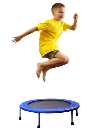 Portrait of a cute  sportive, cheerful happy kid  jumping and dancing on batut. Childhood, freedom, happiness concept. Stock Photo