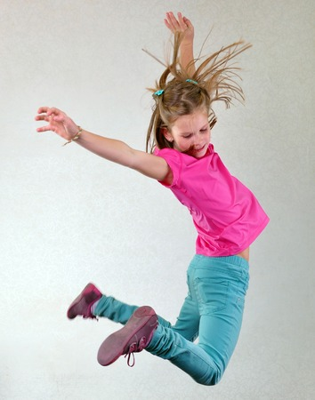 Portrait of a cute sportive, cheerful happy girl jumping and dancing. Childhood, freedom, happiness concept.