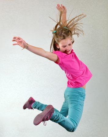 Portret van een leuke sportieve, vrolijke gelukkige meisje springen en dansen. Jeugd, vrijheid, geluk concept. Stockfoto