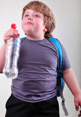 portrait of cute blond schoolboy with a bottle of water photo