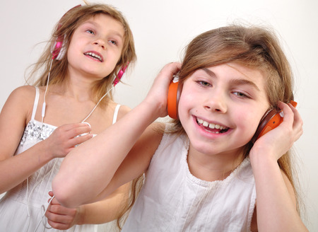 portrait of two little girls with headphones  listening to music and having fun photo