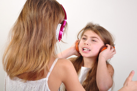 portrait of two children with headphones listening to music photo