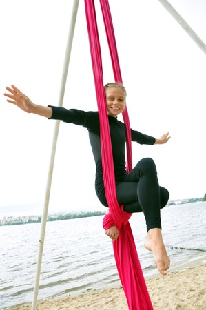 Outdoor activity of cheerful child training on aerial silks or ribbons. Childhood, sports, active lifestyle concept.