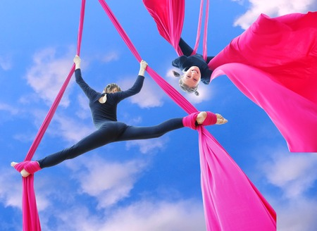 gymnastique: Activité de plein air de la formation de l'enfant gai sur les soies aériennes ou des rubans dans le ciel. Enfance, les sports, le concept de style de vie actif. Banque d'images