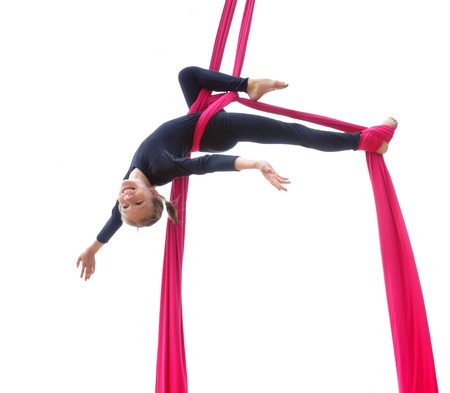 Outdoor activity of cheerful child training on aerial silks or ribbons, hanging upside down. Childhood, sports, active lifestyle concept.