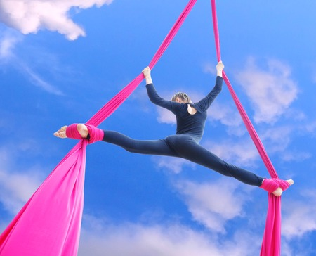 perform: Outdoor activity of cheerful child training on aerial silks or ribbons in the sky.  Childhood, sports, active lifestyle concept.