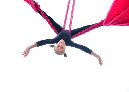 cenital: Activité sonrisa juguetona alegre bailando formación de niños y la realización de las sedas o cintas aéreas, colgado boca abajo. Aislado en blanco. Infancia, el deporte, el concepto de estilo de vida activo.