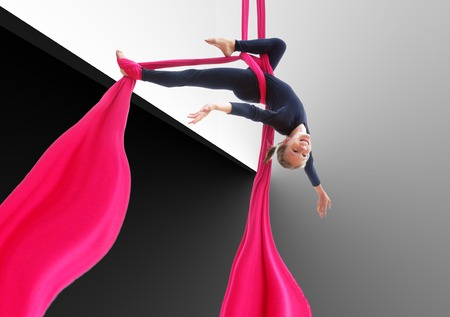 Active smiling sportive cheerful child training dancing performing on aerial silks or ribbons, hanging upside down against black and white background. Childhood, sports, happiness, active lifestyle concept.