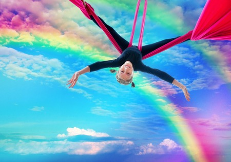 aerial: Active smiling sportive cheerful child training dancing performing on aerial silks or ribbons, hanging upside down in the blue rainbow sky Childhood, sports, happiness, active lifestyle concept.