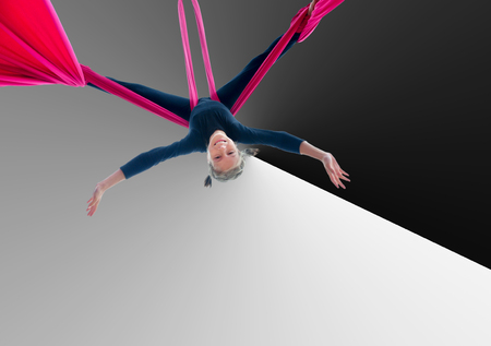 trapeze: Active smiling sportive cheerful child training dancing performing on aerial silks or ribbons, hanging upside down against black and white background. Childhood, sports, happiness, active lifestyle concept.