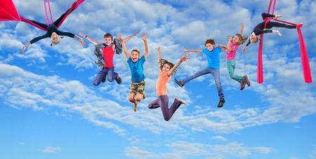 acrobacia: Grupo de salto feliz bailando y sedas aéreas que realizan juntos los niños en el cielo azul.