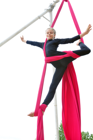 aerial: Active smiling sportive cheerful child training dancing performing and  on aerial silks or ribbons.  Childhood, sports, happiness, active lifestyle concept.