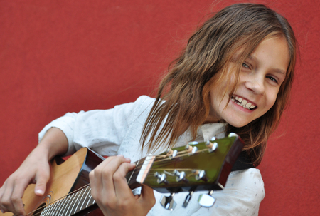perform: Pretty young teen girl playing acoustic guitar in the street. Stock Photo