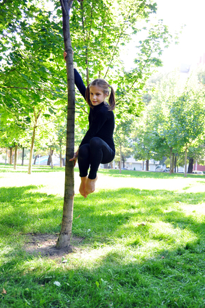 acrobat: Cut? young acrobat having fun outdoor training uses a tree as a gymnastic pole. Stock Photo