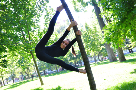 extreme sports: Cute kid having fun outdoor workout uses a tree as a gymnastic pole.
