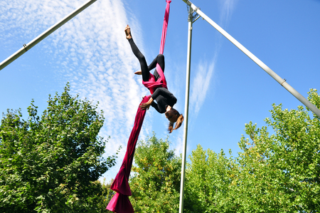 active lifestyle: Outdoor activity of cheerful child training on aerial silks or ribbons. Childhood, sports, active lifestyle concept.