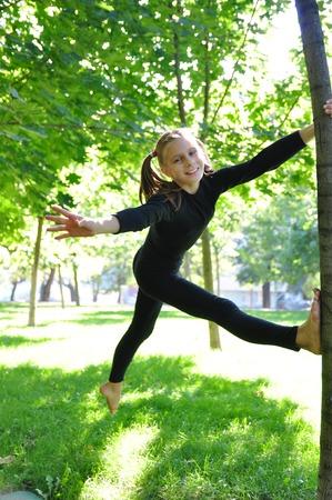 Cute girl having fun outdoor training uses a tree as a gymnastic pole. Stock Photo