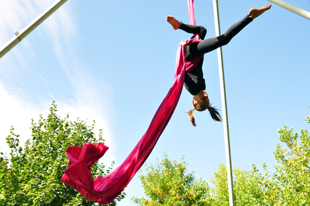 trapeze: Outdoor activity of cheerful child training on aerial silks or ribbons. Childhood, sports, active lifestyle concept.
