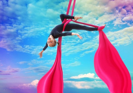 rainbow: Active smiling sportive cheerful child training dancing performing on aerial silks or ribbons, hanging upside down in the blue rainbow sky Childhood, sports, happiness, active lifestyle concept.