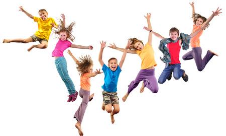 Duża grupa szczęśliwych dzieci wesołych sportowych skoków i taniec. Pojedynczo na białym tle. Dzieciństwo, wolność, pojęcie szczęścia.