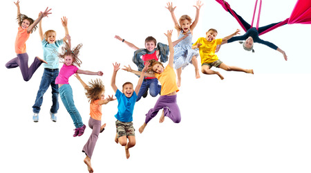 Large group of happy cheerful sportive children jumping and dancing. Isolated over white background. Childhood, freedom, happiness concept. photo