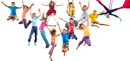 boy gymnast: Large group of happy cheerful sportive children jumping, sporting and dancing. Isolated over white background. Childhood, freedom, happiness, active lifestyle concept. Stock Photo