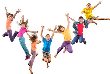 Duża grupa szczęśliwych dzieci wesołych sportowych skoków i taniec. Pojedynczo na białym tle. Dzieciństwo, wolność, pojęcie szczęścia. Zdjęcie Seryjne