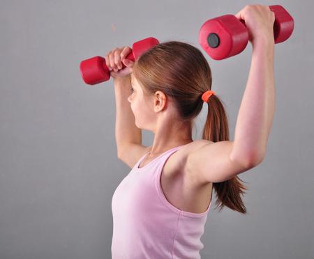 levantar pesas: Adolescente deportiva está haciendo ejercicios para desarrollar músculos aislados sobre fondo gris. Concepto de deporte de estilo de vida saludable. infancia deportivo. Adolescente que ejercita con wieghts.