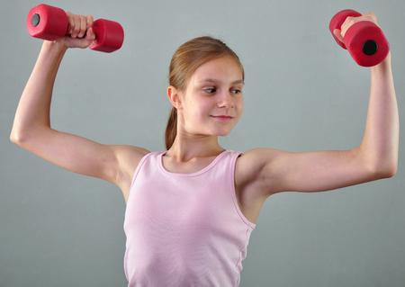 Adolescente deportiva está haciendo ejercicios para desarrollar músculos aislados sobre fondo gris. Concepto de deporte de estilo de vida saludable. infancia deportivo. Adolescente que ejercita con wieghts.