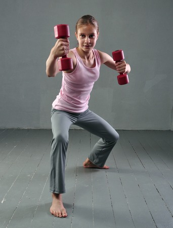teenage girl: Teenage sportive girl is doing exercises with dumbbells to develop muscles on grey background. Stock Photo
