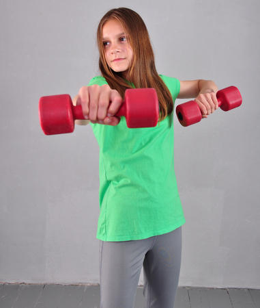 female muscle: Teenage sportive girl is doing exercises with dumbbells to develop muscles isolated on grey background. Sport healthy lifestyle concept. Sporty childhood. Teenager exercising with weights.