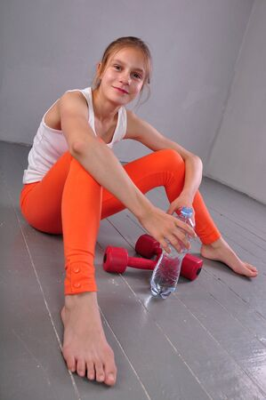 leggings: Indoor portrait of young sportive teen girl with a bottle of drinking water while relaxing a in gym