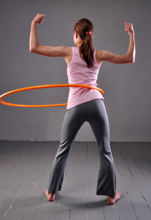 Teenage sportive girl is doing exercises with hula hoop on grey background. Having fun playing game hula-hoop. Sport healthy lifestyle concept. Teenager exercising with tool. photo