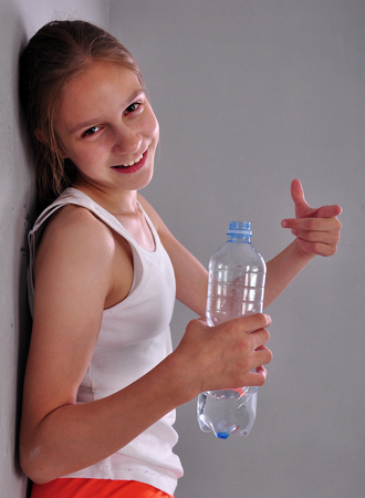 Indoor portrait of young sportive teen girl with a bottle of drinking water while relaxing a in gym leaning against the wall and ponting a sign