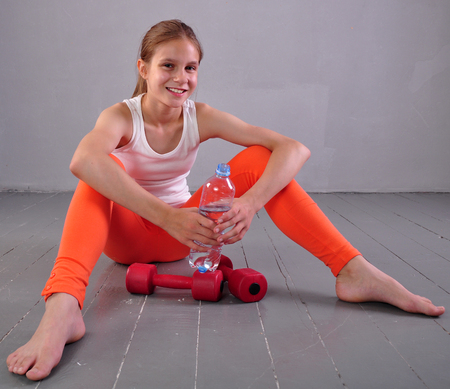 Indoor portrait of young sportive teen girl with a bottle of drinking water while relaxing a in gym photo