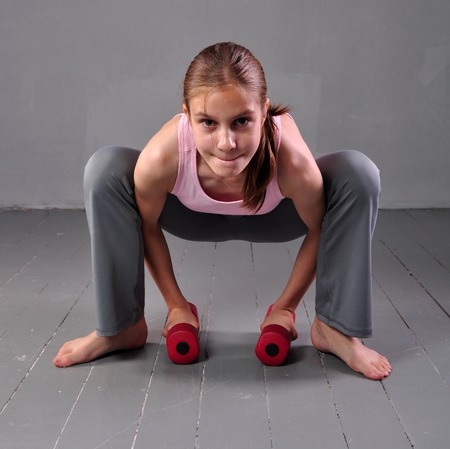 Teenager girl doing exercises with dumbbells to develop with dumbbells muscles on grey background. Sport healthy lifestyle concept. Full length portrait of teen child exercising with weights. photo