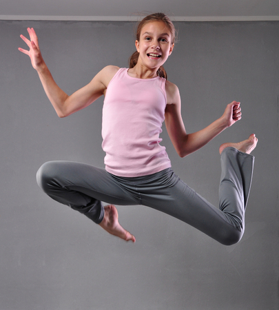 Happy smiling teenage girl dancer jumping and dancing on grey background. photo