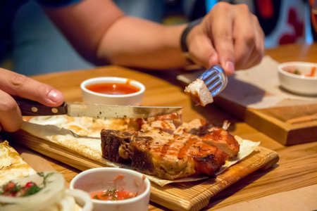 A piece of kebab on a wooden plate, men's hands holding a fork and a knife Stok Fotoğraf