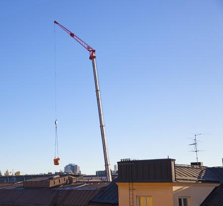 maneuverable: Stockholm, Sweden - July 17, 2016. Crane and roof tops. Editorial