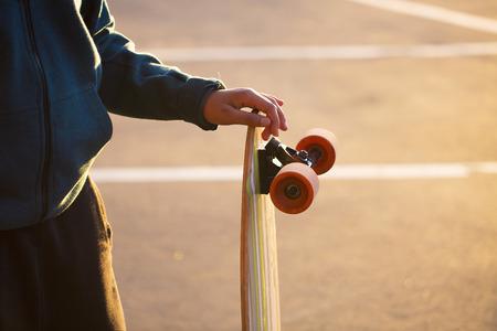 skateboarder: Teenager holding a longboard.
