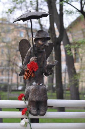 meth: Sculpture of Angel with a book of an elderly man on a bench under an umbrella
