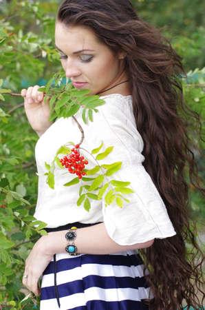 Beautiful girl with long dark hair on his head bowed rowan Stock Photo