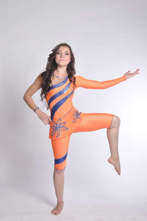 The young beautiful gymnast girl in orange suit smiling Stock Photo