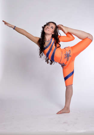 The young beautiful gymnast girl in orange suit