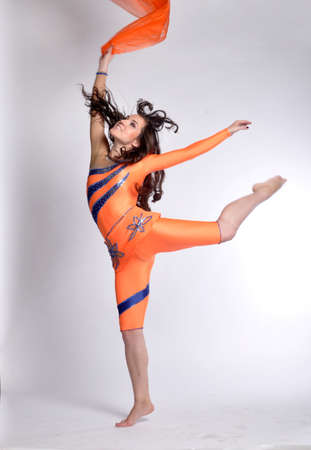 The young beautiful gymnast in orange suit with a scarf Jumping