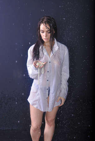 Girl with beads in the hands in the rain Stock Photo
